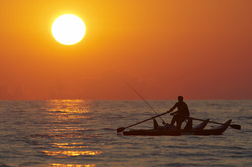 Italy, Forte dei Marmi, Man fishing in boat at sunset - FFF00832