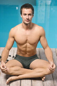 Germany, young man practicing yoga beside swimming pool, portrait - BABF00342