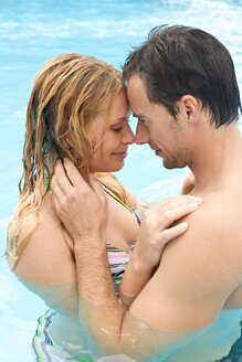 Germany, young couple embracing in swimming pool - BABF00336