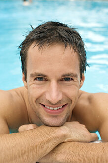 Germany, young man in pool ,smiling, portrait, close-up - BABF00330