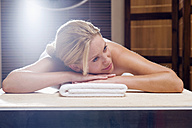 Germany, young woman lying on massage table - BABF00294