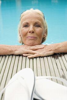 Germany, Senior woman resting on edge of pool, smiling - BABF00285