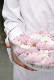 Woman holding bowl of petals in water, close-up, mid section - BABF00279