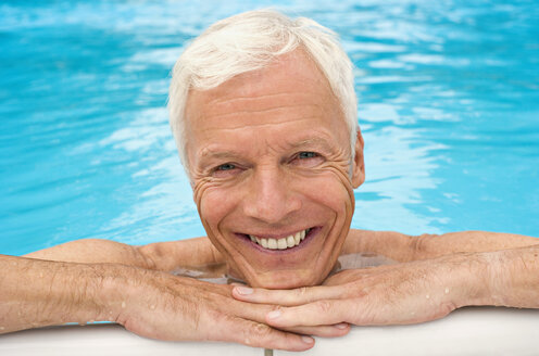 Germany, senior man relaxing in pool, close-up, portrait - BABF00264