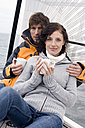 Germany, Baltic Sea, Lübecker Bucht, Young couple on sailing boat sitting and holding mugs, portrait - BAB00401