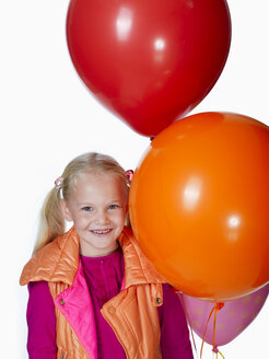 Girl (8-9) holding bunch of balloons, smiling, portrait - KMF01132