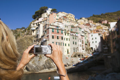 Italy, Liguria, Riomaggiore, Woman photographing houses - MRF01027