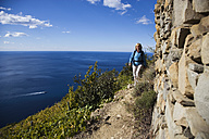 Italy, Liguria, Corniglia, Woman hiking on pathway - MRF00952
