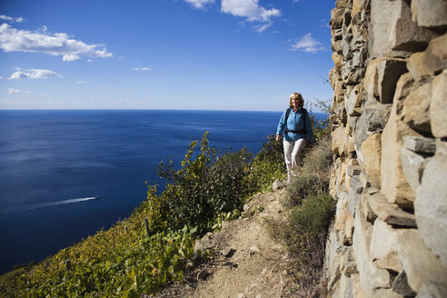 Italy, Liguria, Corniglia, Woman hiking on pathway - MRF00952