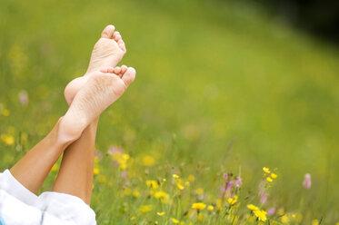 Woman lying in meadow, barefoot - HHF01757