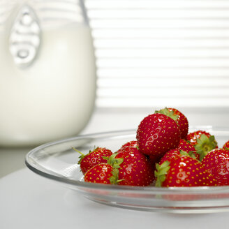 Strawberries on glass plate in front of milk jar, close-up - CHKF00470