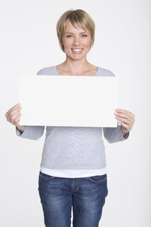 Young woman holding blank placard, portrait - WESTF06852