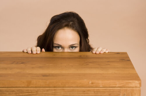 Young woman hiding behind table - RRF00072