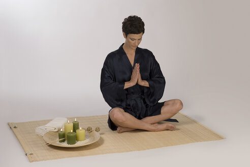 Woman meditating on yoga mat - RRF00039