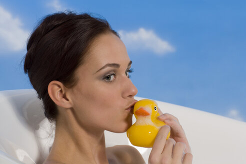 Young woman in bath holding rubber Duck, portrait - RRF00021