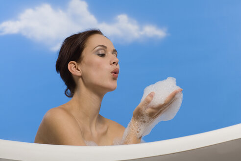Young woman in bubble bath, blowing suds from hands, side view - RRF00015