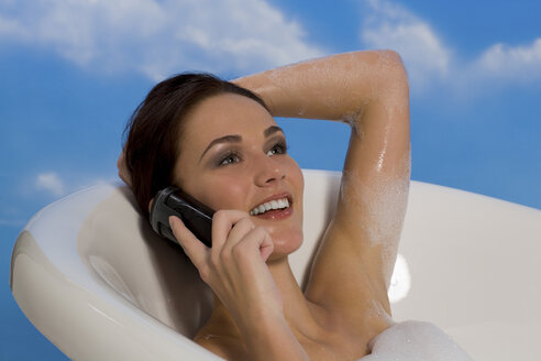 Young woman taking bubble bath and talking on mobile phone - RRF00003