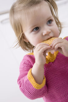 Baby girl (2-3) eating a biskuit, portrait - SMOF00136