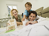 Young family in living room, smiling - WESTF06663