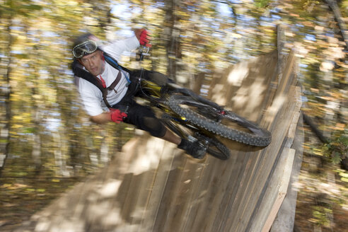 Italy, South Tyrol, Bozen, mountainbiker overcoming an obstacle - FFF00860