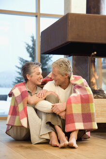Mature couple sitting in front of fireplace - WESTF07752