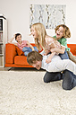 Boy (6-7) and girl (8-9) on father's back in living room - WESTF07342