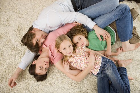 Family lying on floor in living room, elevated view - WESTF07339