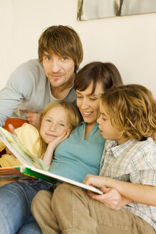 Family reading story book in living room - WESTF07278