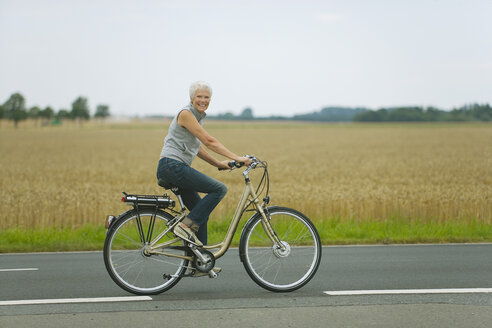 Senior woman biking on road - WESTF07190