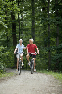 Senior couple biking on forest track - WESTF07140