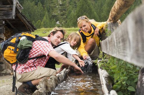 Austria, Salzburger Land, couple with son (8-9) at trough - HHF01814