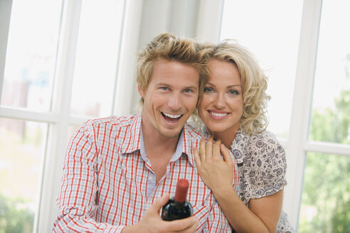 Young couple holding wine bottle, smiling, portrait - HKF00171