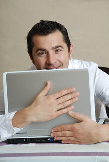 Young man with laptop, portrait - DKF00158