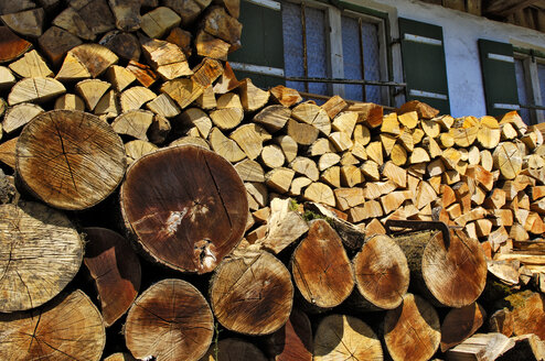 Germany, Endhausen, Firewood stacked under windows of house - MBF00804