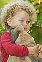 Blonde girl (4-5) with curly hair holding rabbit, portrait - SHF00213