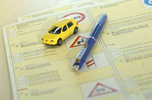 Pen and toy car on driving licence test form - AS03581