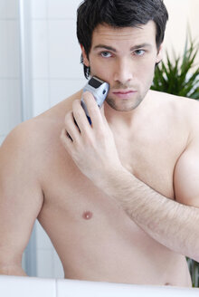 Young man man using electric razor, portrait - VRF00070