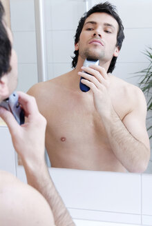 Young man man using electric razor, portrait - VRF00067
