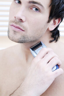 Young man using electric razor, portrait - VRF00064