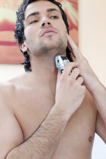 Young man using electric razor, portrait - VRF00061