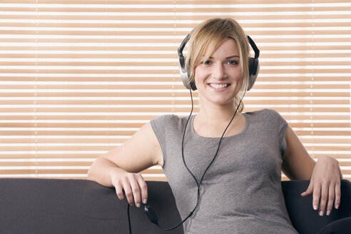 Blonde woman relaxing, smiling, with headphones, portrait - LDF00567
