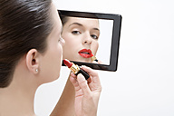 Young woman putting makeup on, portrait - MAEF00998