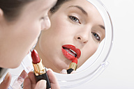 Young woman putting her makeup on, portrait - MAEF00990