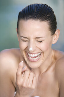 Young woman applying facial cream, portrait, laughing, portrait - ABF00238