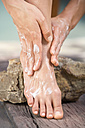 Woman applying lotion to feet, low section - ABF00192