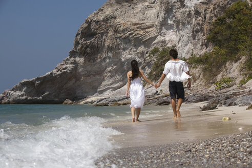 Asia, Thailand, Young couple walking hand in hand along beach, rear view - RDF00655