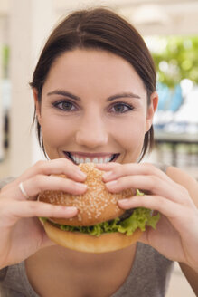 Asia, Thailand, Young woman eating hamburger, smiling, close-up, portrait - RDF00604