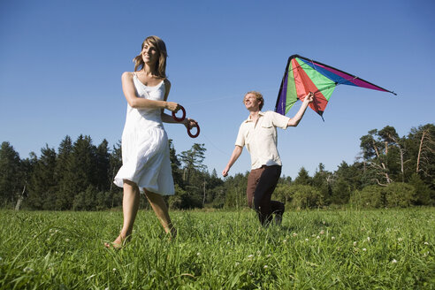 Germany, Bavaria, Young couple flying kites in meadow - RDF00591