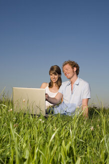 Germany, Bavaria, Young couple in meadow, using laptop, portrait - RDF00557