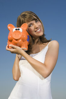 Young woman holding piggy bank, smiling, portrait - RDF00529